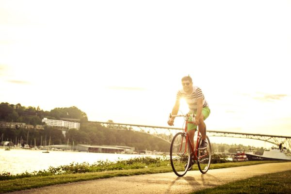 A man riding a bike along a river's edge bike path with a bridge in the background