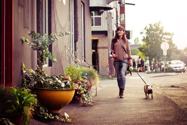 Woman walking on a sidewalk with a dog on a leash