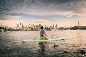 A person kneeling on a paddle board in the water with the Seattle skyline in the background