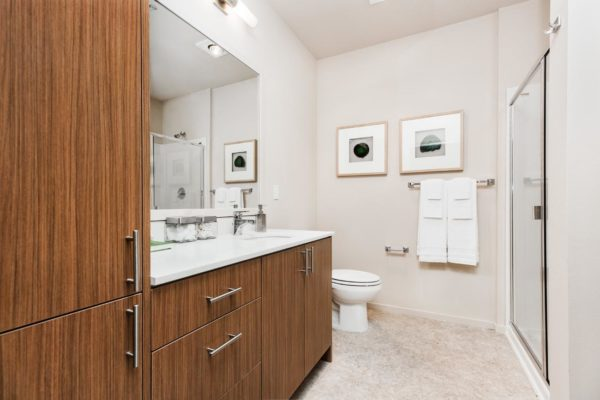 Bathroom at our Fremont Seattle apartments with large, modern cabinets, tile floors, and quartz counters