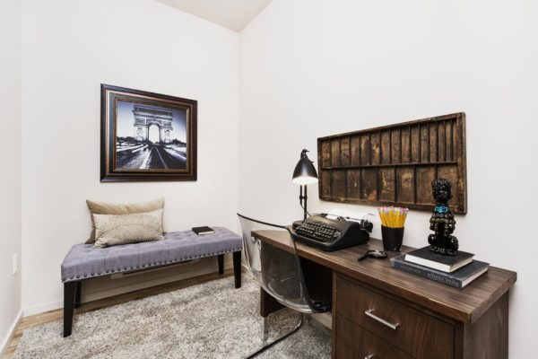 Den area at our Fremont Seattle apartments with a brown wood desk that has a typewriter on top of it