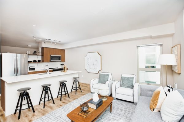 Interior of our Fremont Seattle apartments with hardwood floors, white walls, and a large kitchen with an island