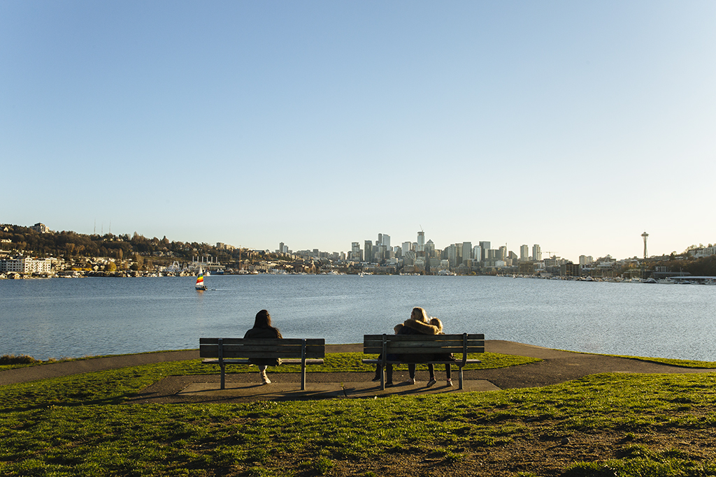 Two women sitting on benches looking out on to the water