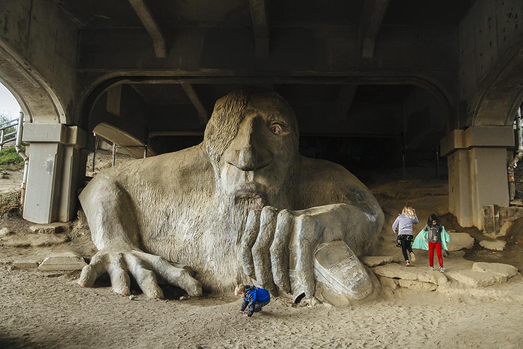 A large stone sculpture of a man under a bridge