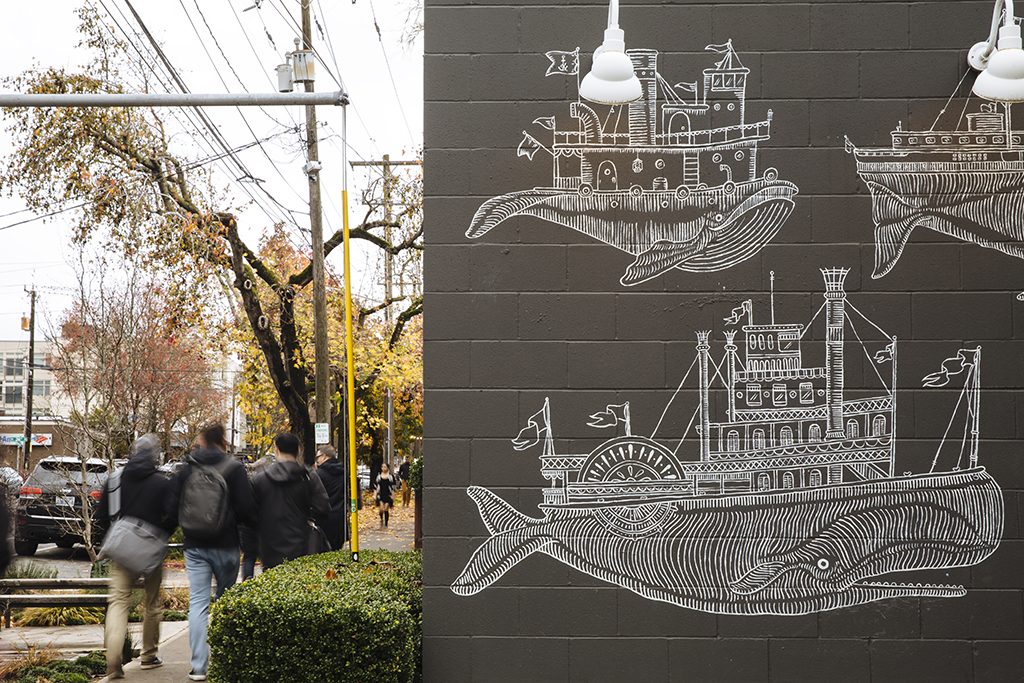 A black brick wall with whale drawings on it and people walking in the background