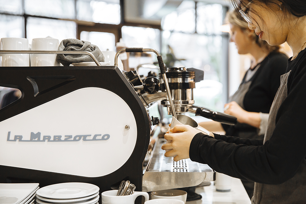 Two women making cappuccinos